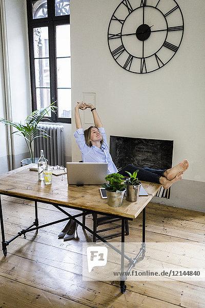 Entspannte Frau sitzt zu Hause am Schreibtisch mit erhobenen Füßen
