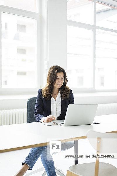 Lächelnde Geschäftsfrau sitzt am Schreibtisch im Büro und arbeitet am Laptop.