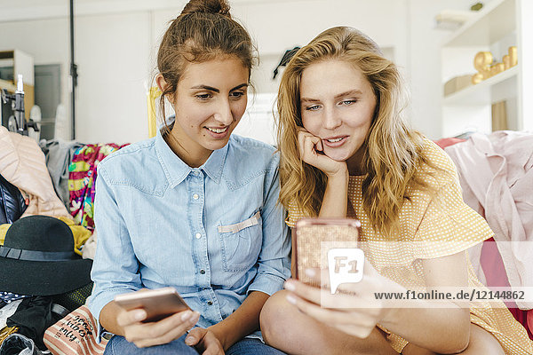 Two young women sitting on couch using cell phones surrounded by fashion