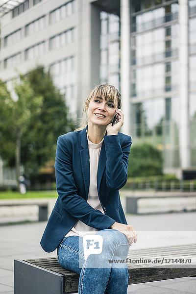Lächelnde Geschäftsfrau sitzt auf der Bank und redet auf dem Handy im Freien.