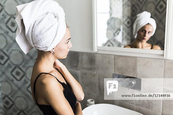 Junge Frau mit Haaren in ein Handtuch gehüllt  das in den Badezimmerspiegel schaut.