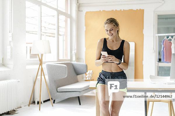 Lächelnde junge Frau in Sportbekleidung beim Blick aufs Handy