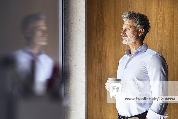 Spiegelung des reifen Geschäftsmannes mit Kaffeetasse