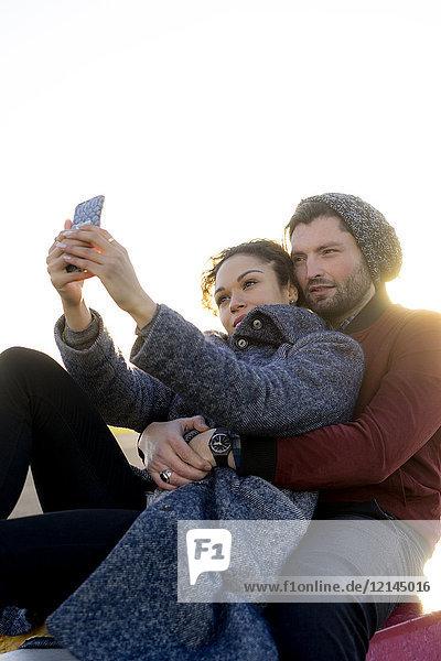 Junges Paar mit Selfie im Freien