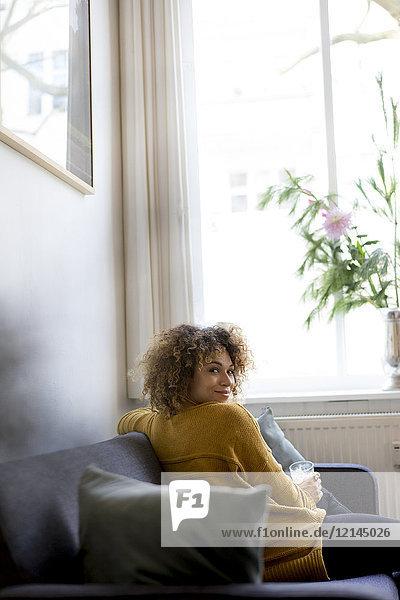 Porträt einer lächelnden jungen Frau  die zu Hause auf der Couch sitzt.
