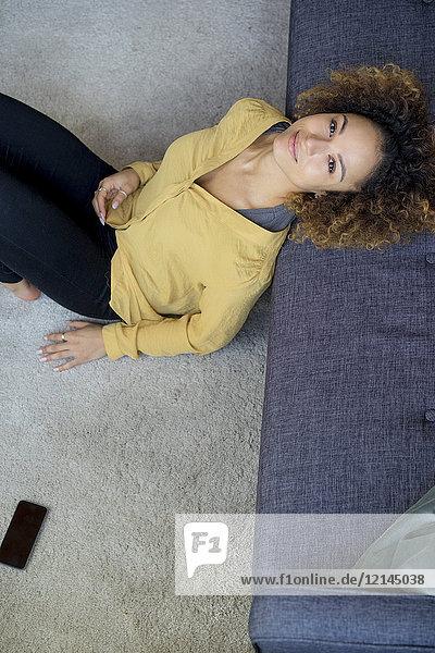Porträt einer lächelnden jungen Frau  die sich zu Hause auf die Couch lehnt.