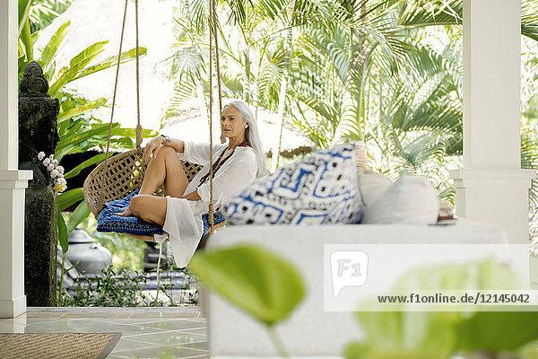 Attraktive Seniorin entspannt im Hängesessel