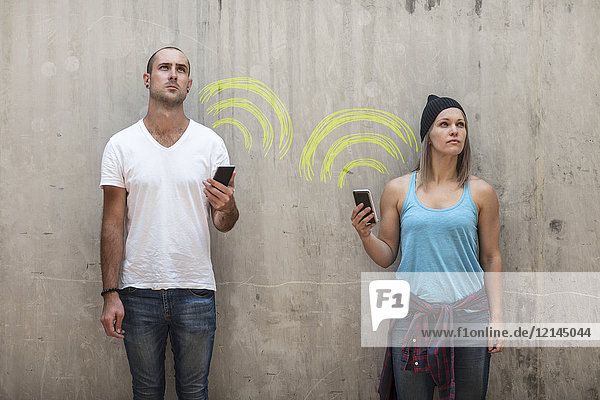 Man and woman holding their phones with wifi sign in chalk