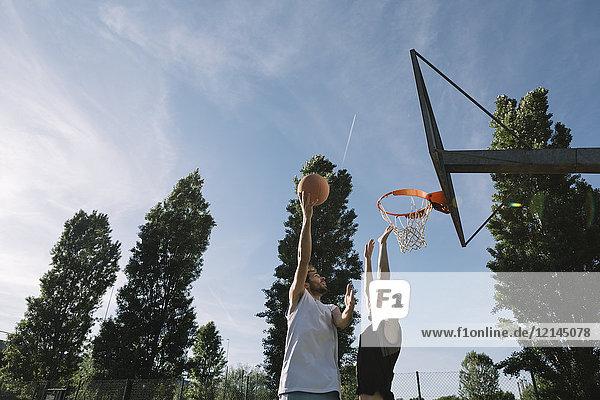 Männer spielen Basketball