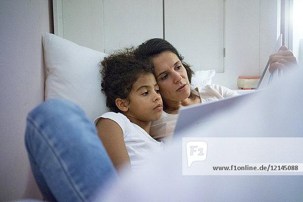 Mutter und Tochter im Bett liegend  Kinderbuch lesend