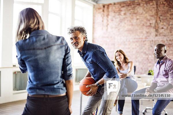 Kollegen beim Basketball im Büro
