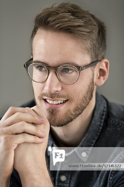 Porträt eines lächelnden jungen Mannes mit Brille