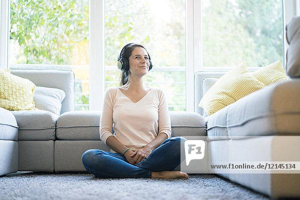 Frau sitzt allein auf der Couch und hört Musik mit Kopfhörern.