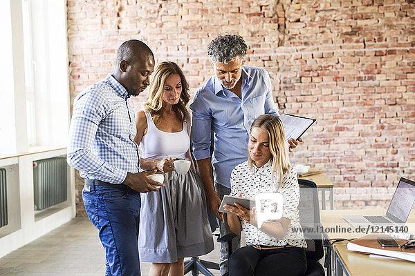 Geschäftsfrau teilt sich Tablettenkollegen am Schreibtisch im Büro