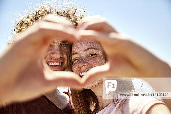 Glückliches junges Paar  das mit den Händen ein Herz formt.