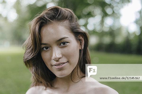 Porträt der attraktiven brünetten jungen Frau im Freien