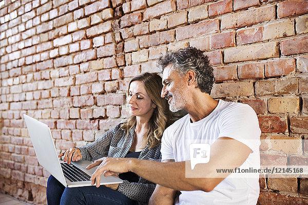 Geschäftsmann und Frau im Loft sitzend  mit Laptop  Gründung eines Start-up-Unternehmens