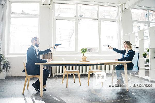 Geschäftsfrau und Geschäftsmann zielen mit Waffen im Amt