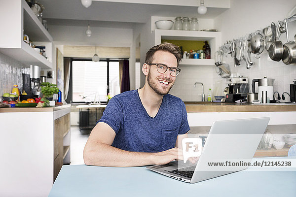 Portrait of smiling man using laptop in kitchen at home