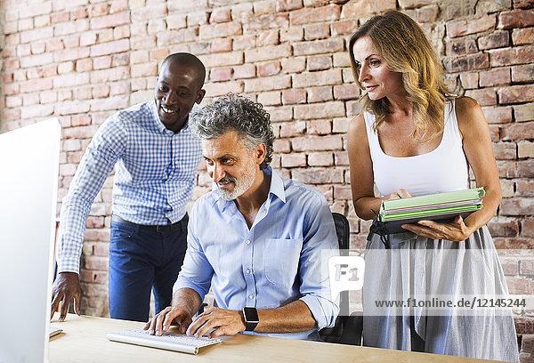 Lächelnde Kollegen bei der Zusammenarbeit am Schreibtisch im Büro