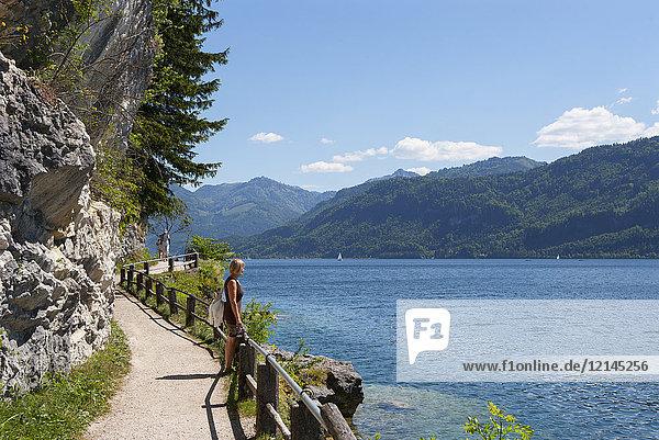 Austria  Salzkammergut  Salzburg State  Sankt Gilgen  Wolfgangsee  female hiker on waterfront promenade