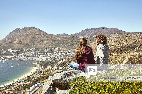 Südafrika  Kapstadt  junges Paar an der Küste sitzend mit Blick auf das Meer