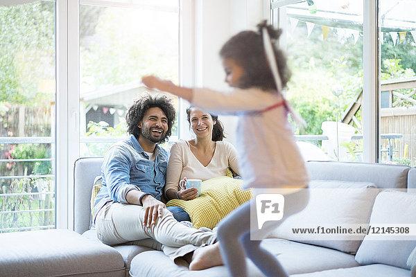 Eltern sitzen auf der Couch  während die Tochter springt und sich amüsiert.