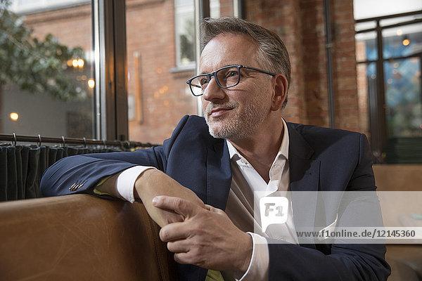 Portrait of content businessman waiting in a restaurant