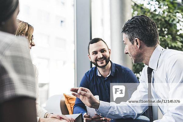 Lächelnder Geschäftsmann bei einem Treffen mit Kollegen