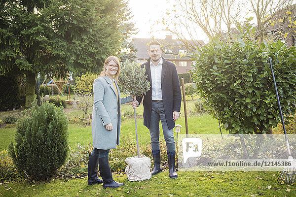 Porträt eines lächelnden Paares  das im Garten steht und im Herbst einen Baum pflanzt.