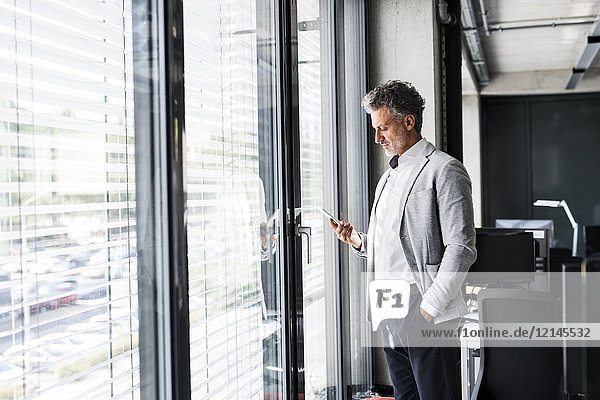 Mature businessman standing at the window in office holding cell phone