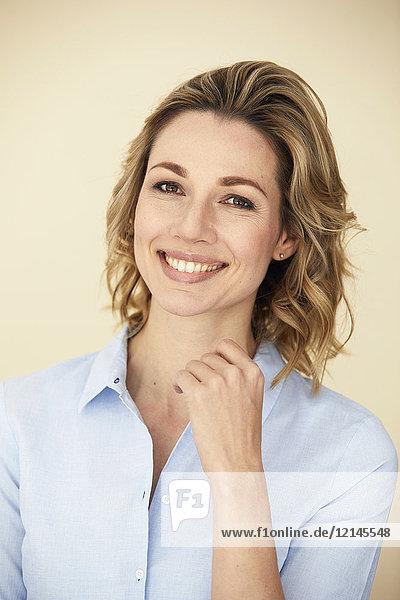 Porträt einer blonden Frau  lächelnd  Geschäftsfrau  hellblaue Bluse