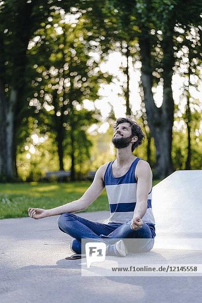 Mann im Skatepark sitzend meditierend