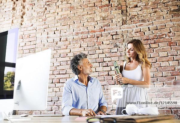 Zwei Kollegen arbeiten zusammen am Schreibtisch im Büro