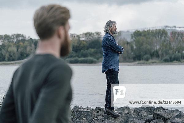 Vater und Sohn verbringen Zeit zusammen am Fluss,  Vater steht auf Steinen.