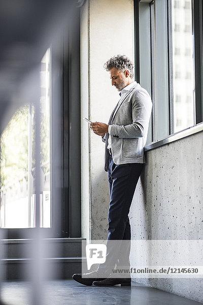 Erwachsener Geschäftsmann  der am Fenster steht und ein Handy hält