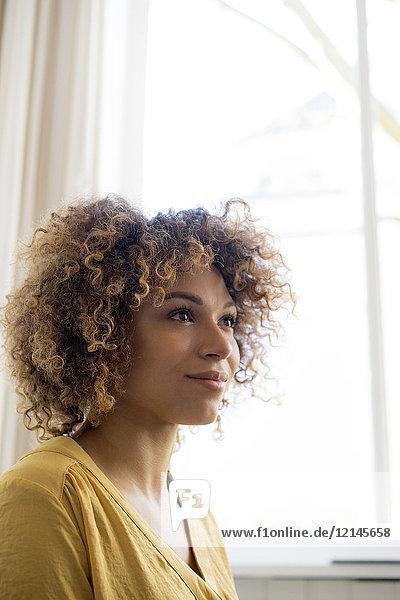 Porträt einer lächelnden jungen Frau am Fenster