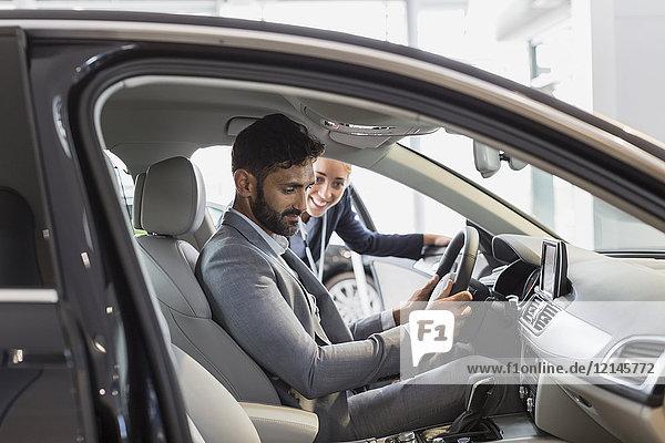 Autoverkäuferin und männlicher Kunde am Fahrersitz des Neuwagens im Autohaus Showroom