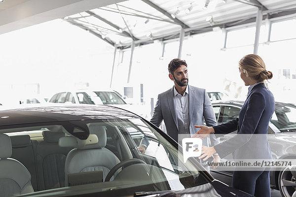 Autoverkäuferin zeigt Neuwagen dem männlichen Kunden im Autohaus-Showroom