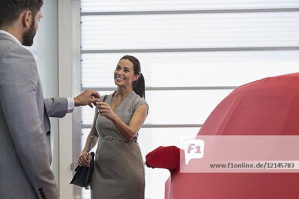 Autoverkäufer übergibt Autoschlüssel an lächelnde Kundin im Autohaus-Showroom