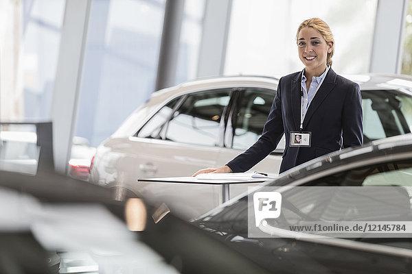 Portrait lächelnde  selbstbewusste Autoverkäuferin im Autohaus-Showroom