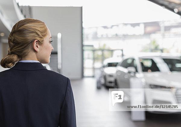 Blonde Autoverkäuferin schaut weg im Autohaus-Showroom