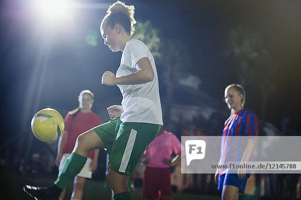 Junge Fußballspielerin, die nachts auf dem Spielfeld trainiert.