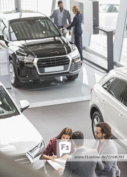Autoverkäufer und Kunden im Autohaus Showroom