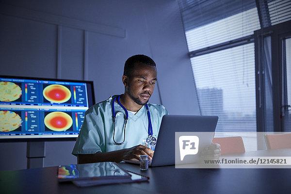 Fokussierter Chirurg am Laptop im Krankenhaus