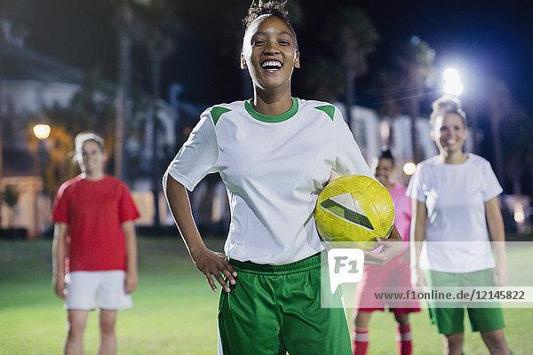 Portrait selbstbewusst, lachende junge Fußballspielerin, die nachts auf dem Spielfeld trainiert.