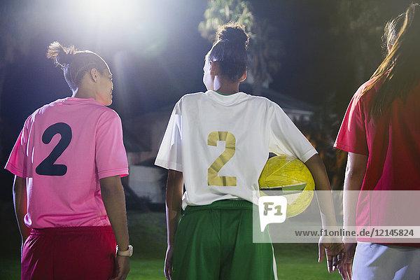 Junge Fußballspielerinnen mit Ball auf dem Spielfeld bei Nacht