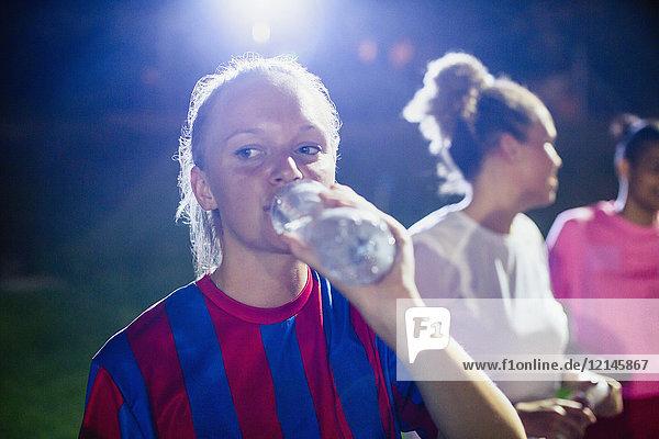 Junge Fußballspielerin beim Trinken aus der Wasserflasche