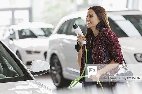 Lächelnde Kundin mit Hybrid-Ladekabel im Autohaus
