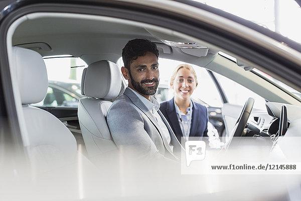 Portrait lächelnde  selbstbewusste Autoverkäuferin und männliche Kundin im Fahrerset des Neuwagens im Autohaus